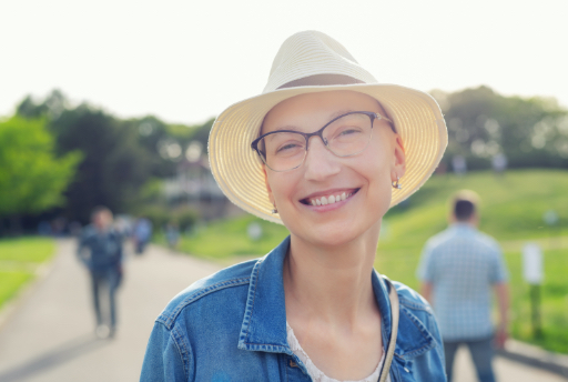 woman with tan hat walks in a park